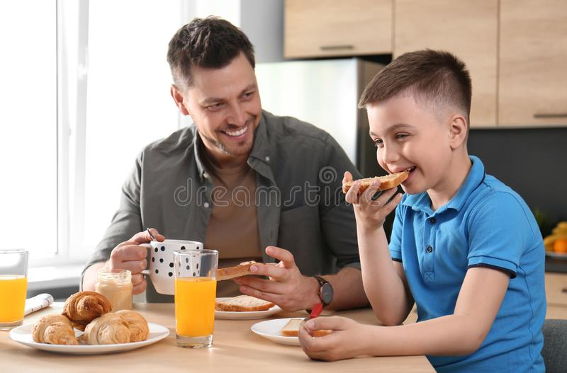 Dad and son having breakfast  in kitchen royalty free stock photography