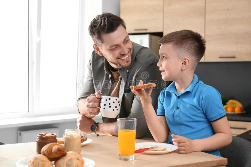 Dad and son having breakfast together in stock image