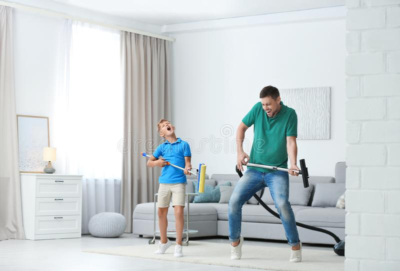 Dad and son having fun while cleaning living room stock photos
