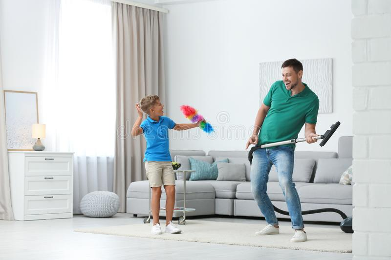 Dad and son having fun while cleaning living room stock image