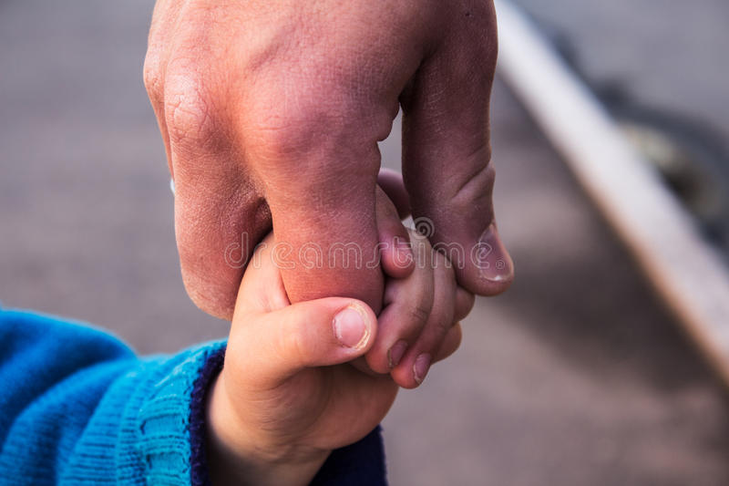 Dad and son holding hands stock photos