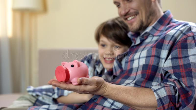 Dad and son holding piggy-bank and smiling, social welfare, health insurance royalty free stock images
