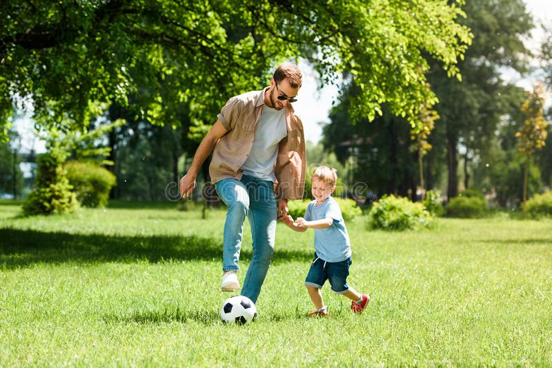 dad and son playing football royalty free stock photo