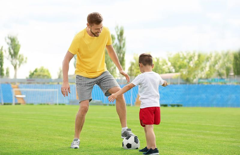 Dad and son playing football together. stock image