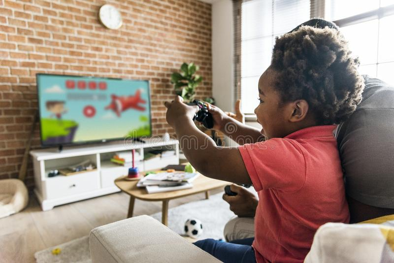 Dad and son playing game at living room together stock photos