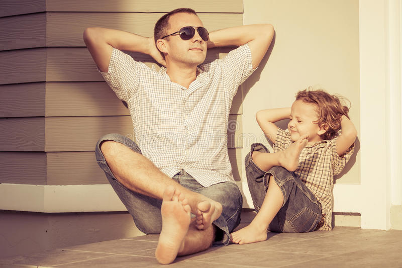 Dad and son playing near a house stock photos