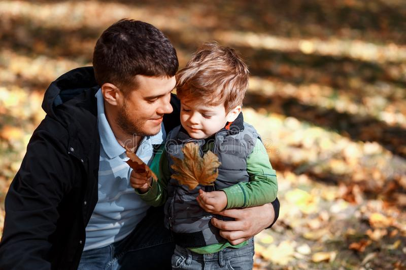 Dad and son playing outside in autumn in the park royalty free stock images