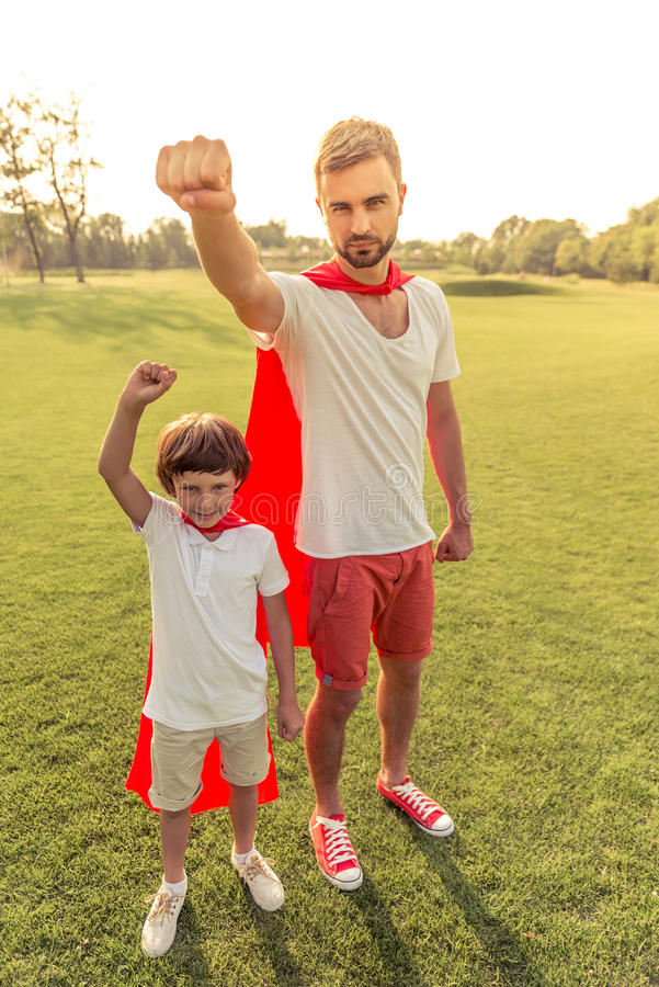 Dad and son playing superheroes stock image