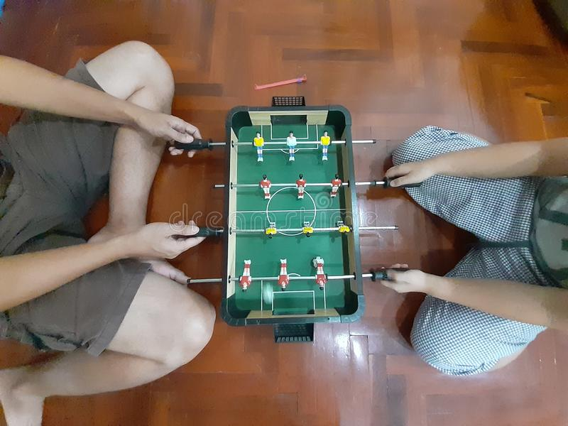 Dad and son are playing the table football together stock photos