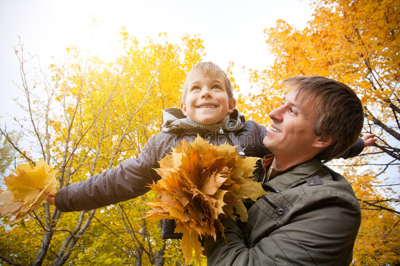 Download Dad And Son Are Playing In A Yellow Autumn Park Stock Photo - Image: 33383808