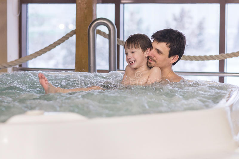 Dad and son relax in the tub. With hydro massage in Spa salon royalty free stock photos