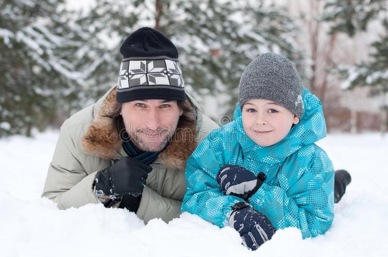 Dad and son rest in the snow. In the park