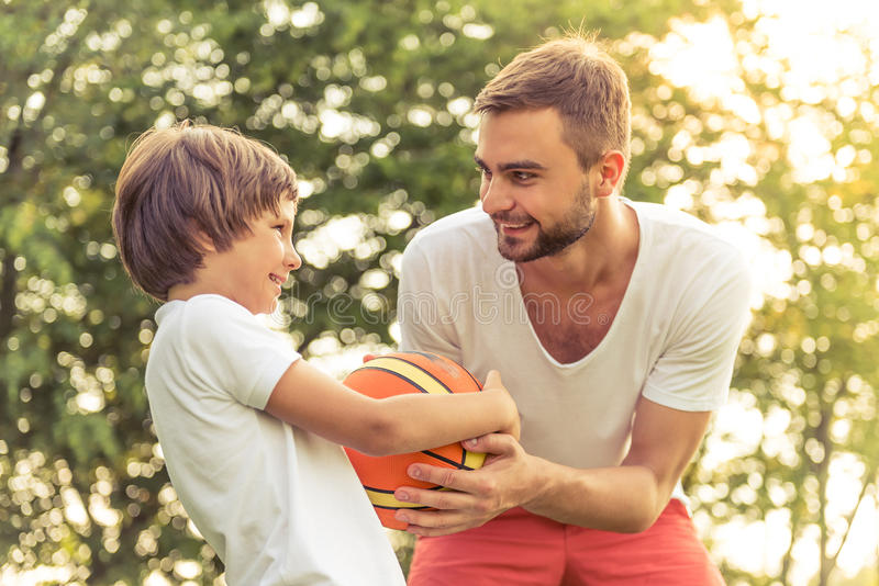 Dad and son resting outdoors. Cute little boy and his handsome young dad are smiling while playing a ball in the park stock image
