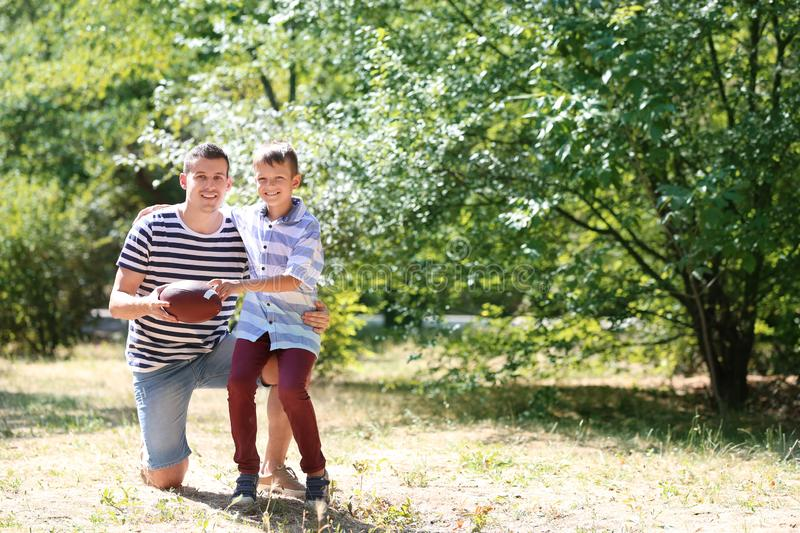 Dad and son with rugby ball outdoors royalty free stock image
