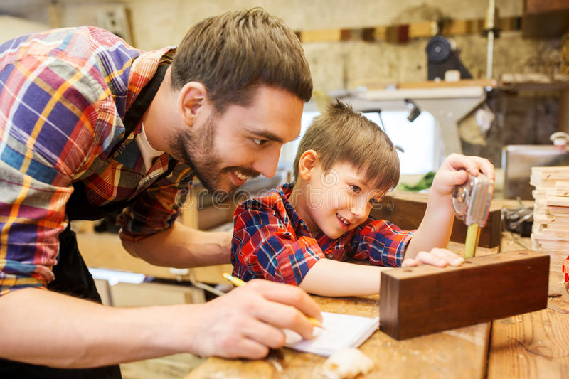 Dad and son with ruler measuring plank at workshop royalty free stock image