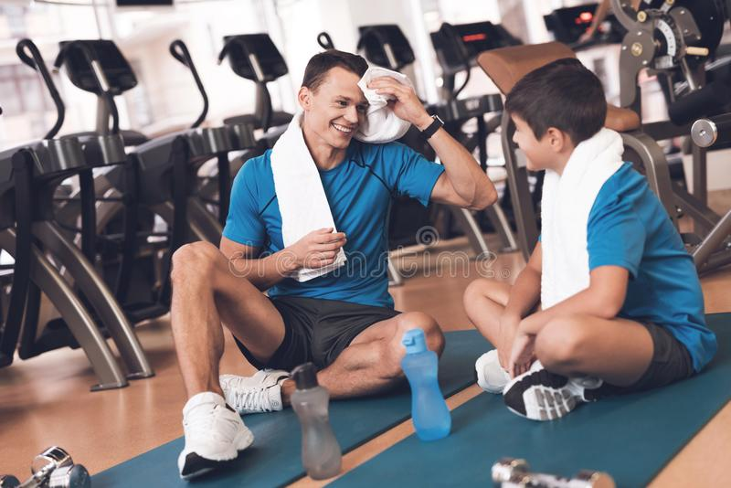 Dad and son in the same clothes in gym. Father and son lead a healthy lifestyle. royalty free stock images