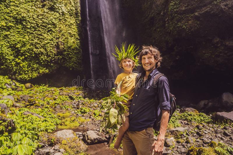 Dad and son at the Sekumpul waterfalls in jungles on Bali island, Indonesia. Bali Travel Concept.  royalty free stock photo