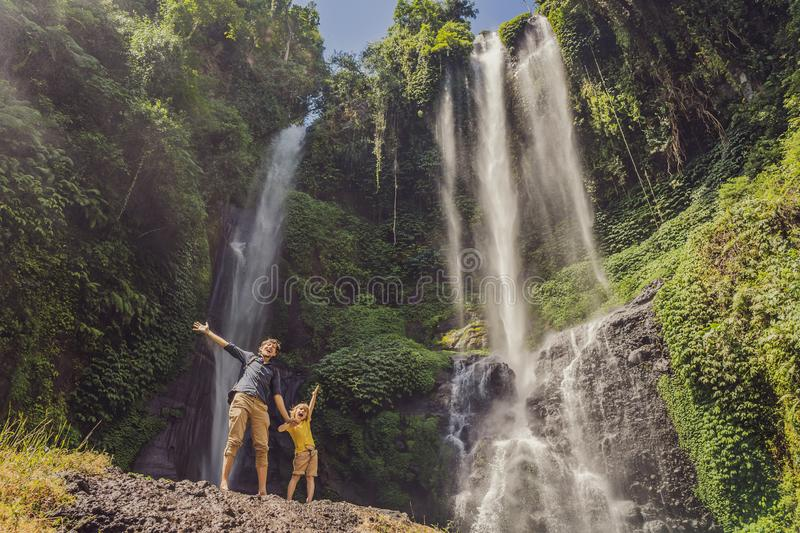Dad and son at the Sekumpul waterfalls in jungles on Bali island, Indonesia. Bali Travel Concept.  stock image