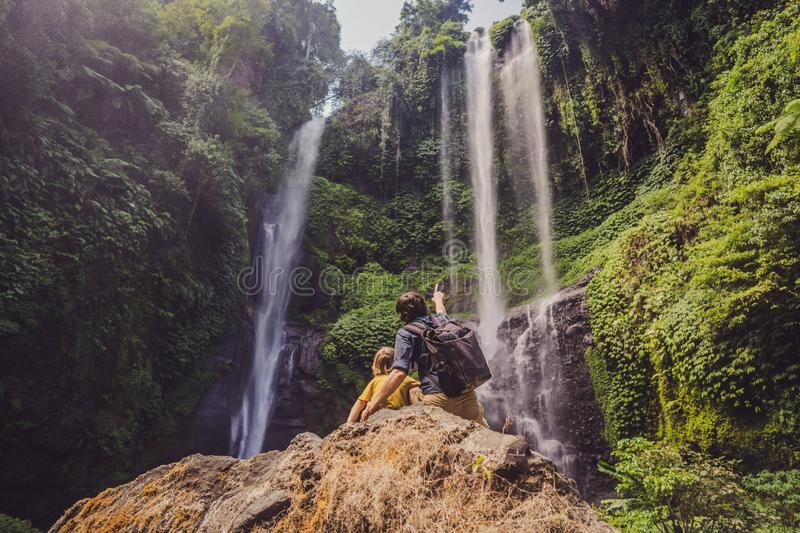Dad and son at the Sekumpul waterfalls in jungles on Bali island, Indonesia. Bali Travel Concept.  stock photo