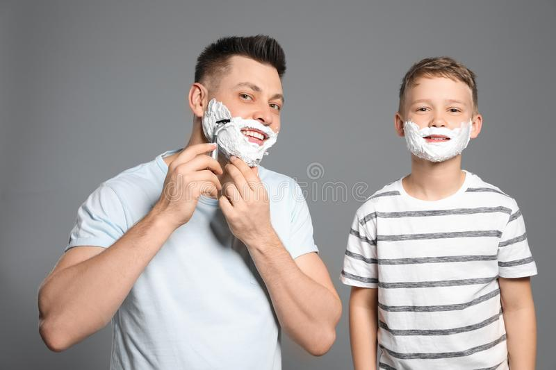 Dad and son with shaving foam on faces. Grey background royalty free stock image