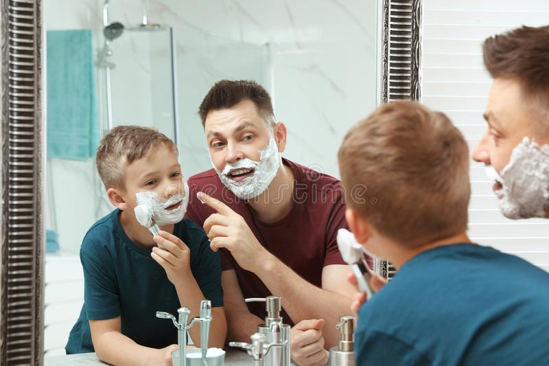 Dad and son with shaving foam. At mirror stock images
