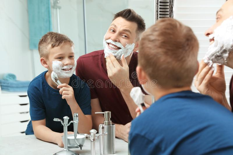 Dad and son with shaving foam. At mirror royalty free stock photo