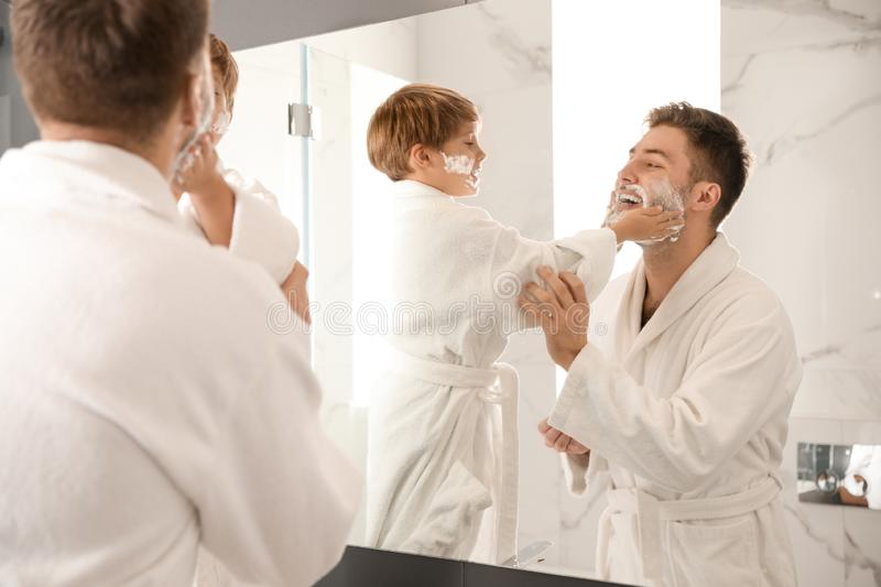 Dad and son with shaving foam on their faces having fun. In bathroom stock image