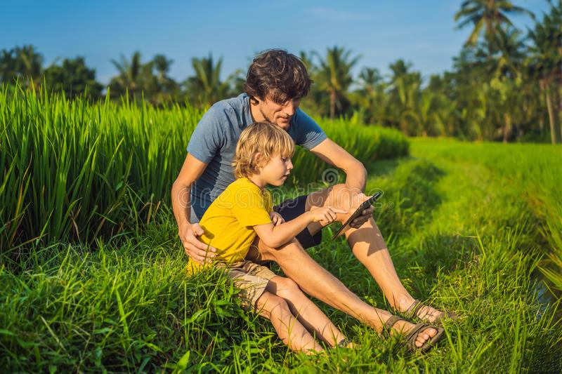 Dad and son sitting on the field holding tablet. Boy sitting on the grass on sunny day. Home schooling or playing a. Tablet stock photography