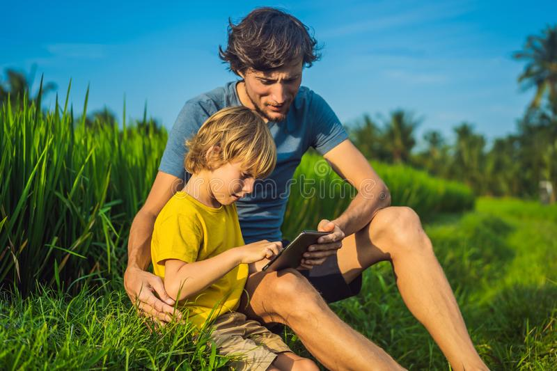 Dad and son sitting on the field holding tablet. Boy sitting on the grass on sunny day. Home schooling or playing a. Tablet royalty free stock image