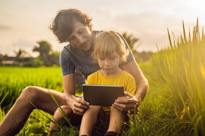 Dad and son sitting on the field holding tablet. Boy sitting on the grass on sunny day. Home schooling or playing a. Tablet stock image