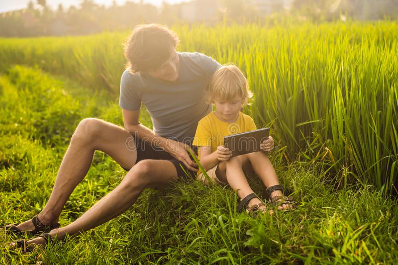 Dad and son sitting on the field holding tablet. Boy sitting on the grass on sunny day. Home schooling or playing a. Tablet royalty free stock photo