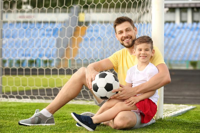 Dad and son with soccer ball stock photos