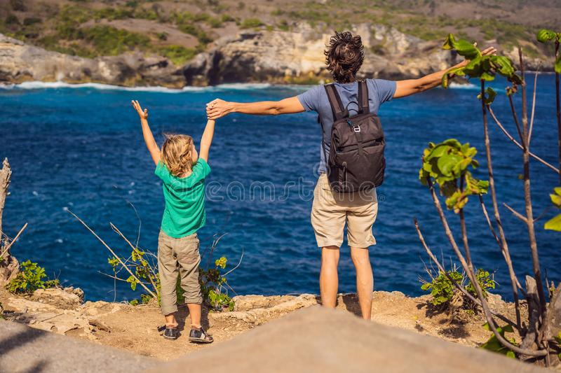 Dad and son tourists against the background of the sea Angel`s Billabong in Nusa Penida, Bali, Indonesia. Travel to Bali royalty free stock images