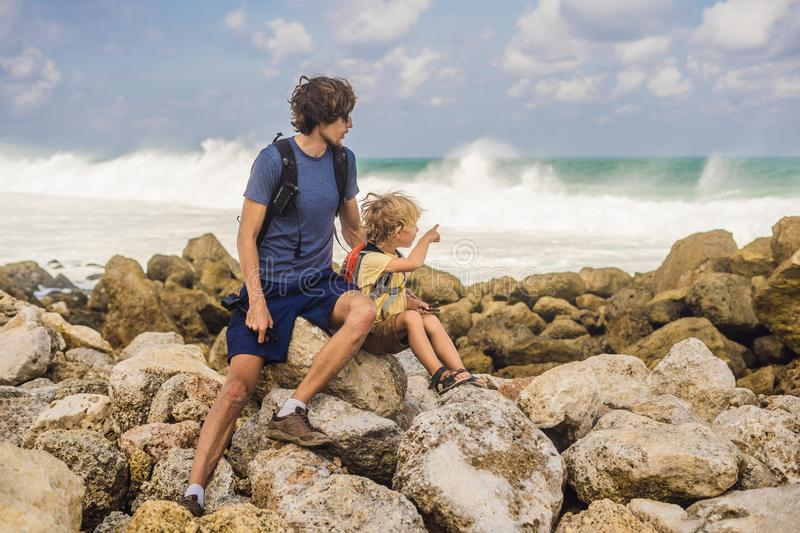 Dad and son travelers on amazing Melasti Beach with turquoise water, Bali Island Indonesia. Traveling with kids concept.  stock image
