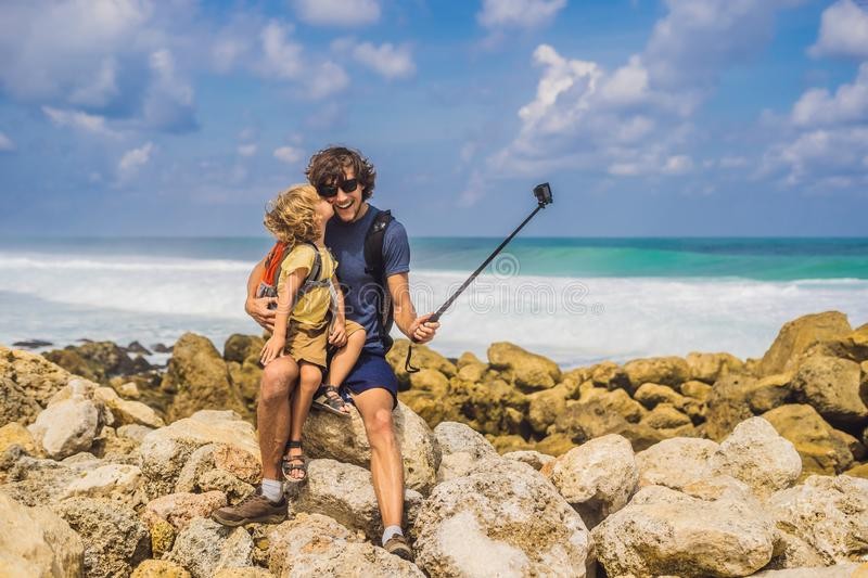 Dad and son travelers on amazing Melasti Beach with turquoise water, Bali Island Indonesia. Traveling with kids concept.  royalty free stock images