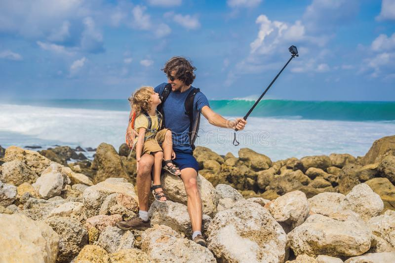 Dad and son travelers on amazing Melasti Beach with turquoise water, Bali Island Indonesia. Traveling with kids concept.  stock photo