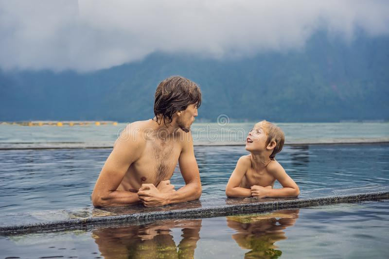 Dad and son travelers in Hot Springs in Bali on the background of lake. Traveling with children concept.  stock image