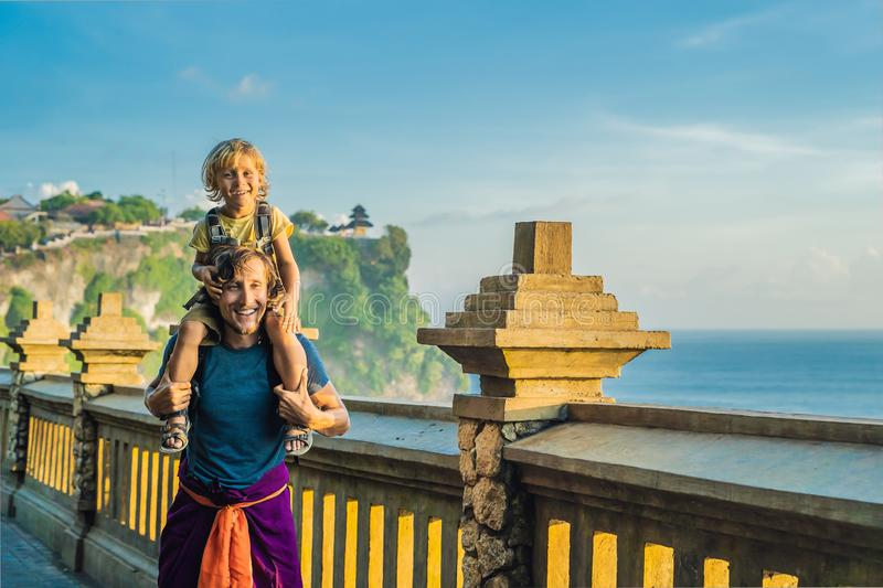 Dad and son travelers in Pura Luhur Uluwatu temple, Bali, Indonesia. Amazing landscape - cliff with blue sky and sea. Traveling w. Ith kids concept stock photos