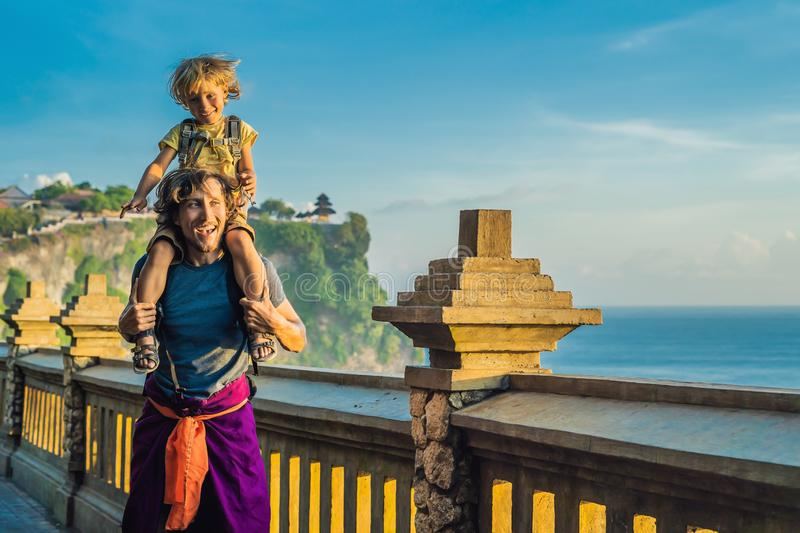 Dad and son travelers in Pura Luhur Uluwatu temple, Bali, Indonesia. Amazing landscape - cliff with blue sky and sea. Traveling w. Ith kids concept stock photo