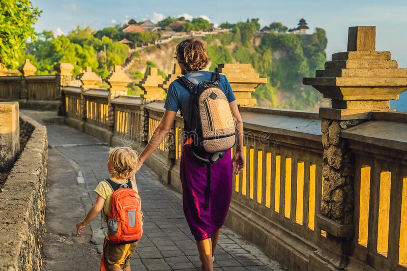 Dad and son travelers in Pura Luhur Uluwatu temple, Bali, Indonesia. Amazing landscape - cliff with blue sky and sea. Traveling wi. Th kids concept stock photo