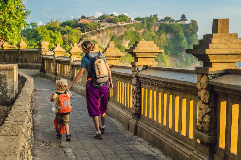 Dad and son travelers in Pura Luhur Uluwatu temple, Bali, Indonesia. Amazing landscape - cliff with blue sky and sea. Traveling wi. Th kids concept royalty free stock image