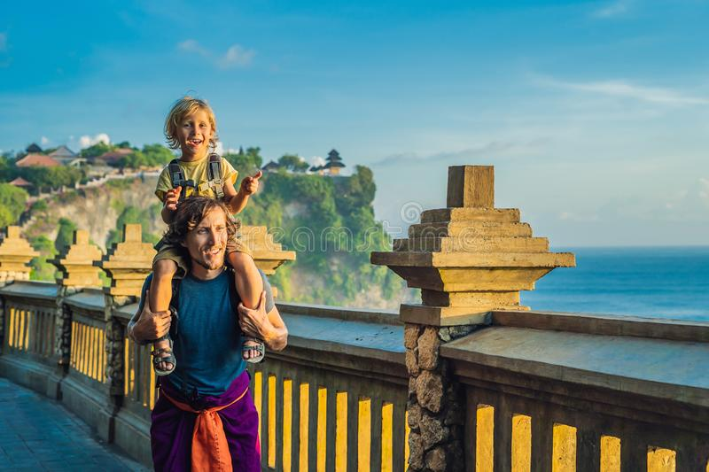 Dad and son travelers in Pura Luhur Uluwatu temple, Bali, Indonesia. Amazing landscape - cliff with blue sky and sea. Traveling wi. Th kids concept stock photography