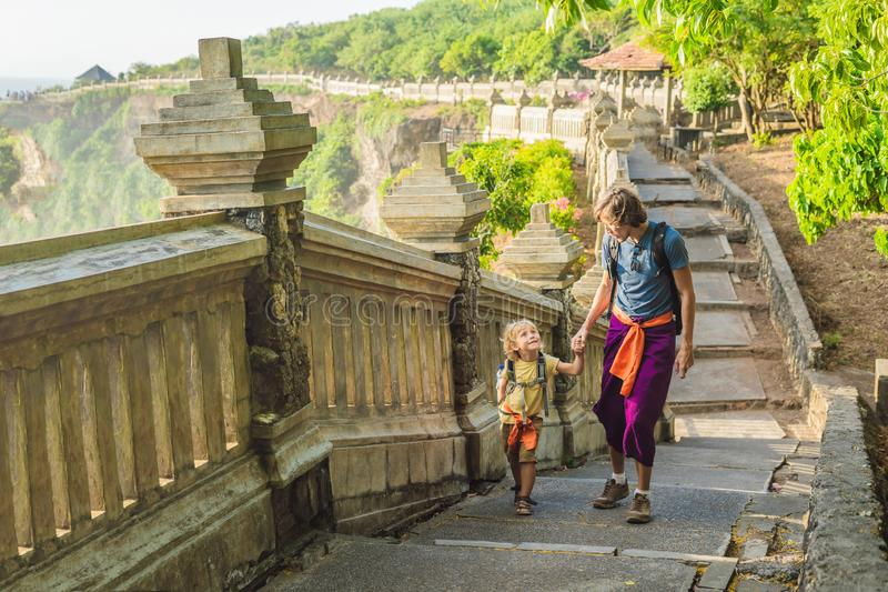 Dad and son travelers in Pura Luhur Uluwatu temple, Bali, Indonesia. Amazing landscape - cliff with blue sky and sea stock photography