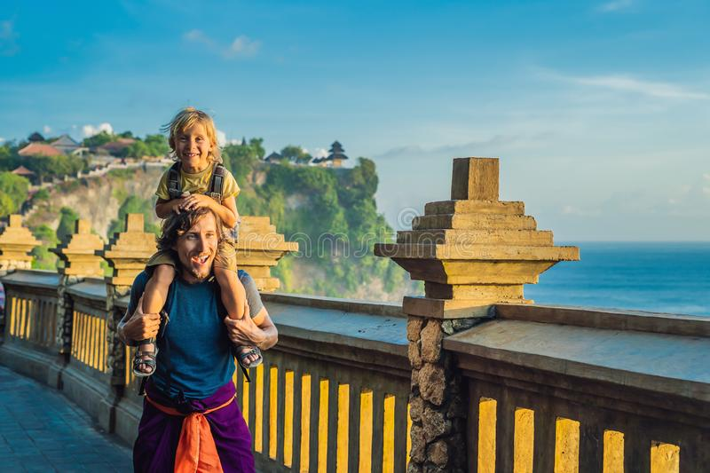 Dad and son travelers in Pura Luhur Uluwatu temple, Bali, Indonesia. Amazing landscape - cliff with blue sky and sea stock image