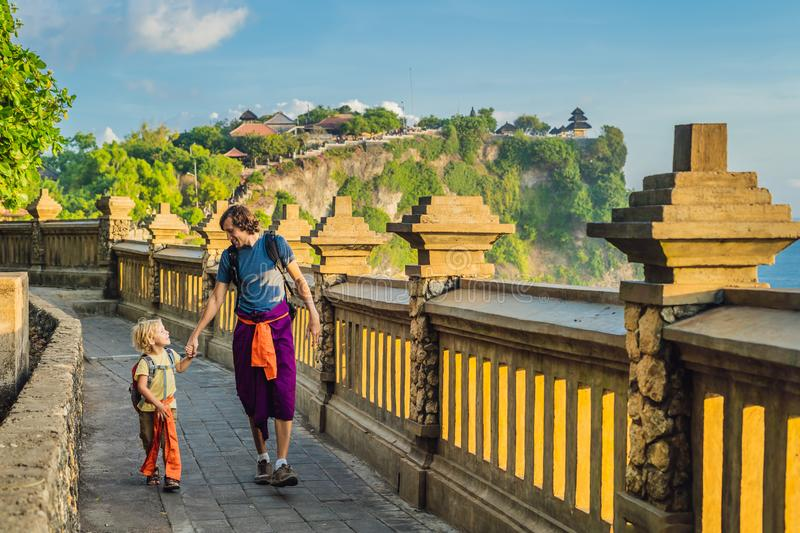 Dad and son travelers in Pura Luhur Uluwatu temple, Bali, Indonesia. Amazing landscape - cliff with blue sky and sea. Traveling wi. Th kids concept royalty free stock photo