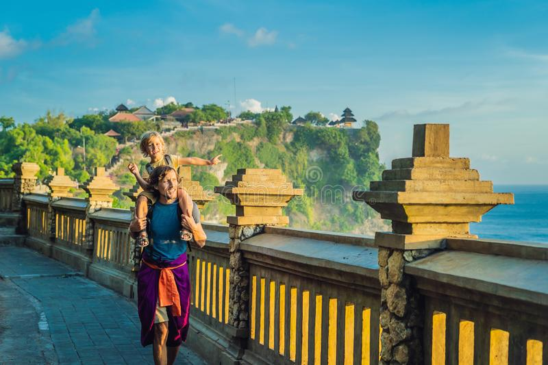 Dad and son travelers in Pura Luhur Uluwatu temple, Bali, Indonesia. Amazing landscape - cliff with blue sky and sea. Traveling wi. Th kids concept royalty free stock photos