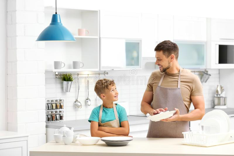 Dad and son wiping dishes royalty free stock image