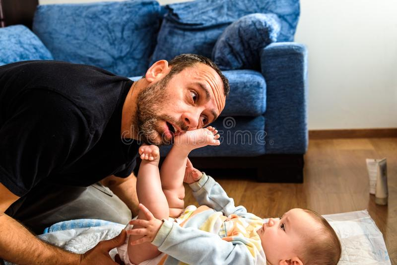 Dad struggling with his baby daughter to change dirty diapers putting faces of effort, concept of fatherhood.  royalty free stock photo