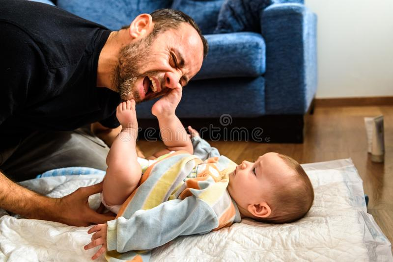 Dad struggling with his baby daughter to change dirty diapers putting faces of effort, concept of fatherhood.  royalty free stock photography
