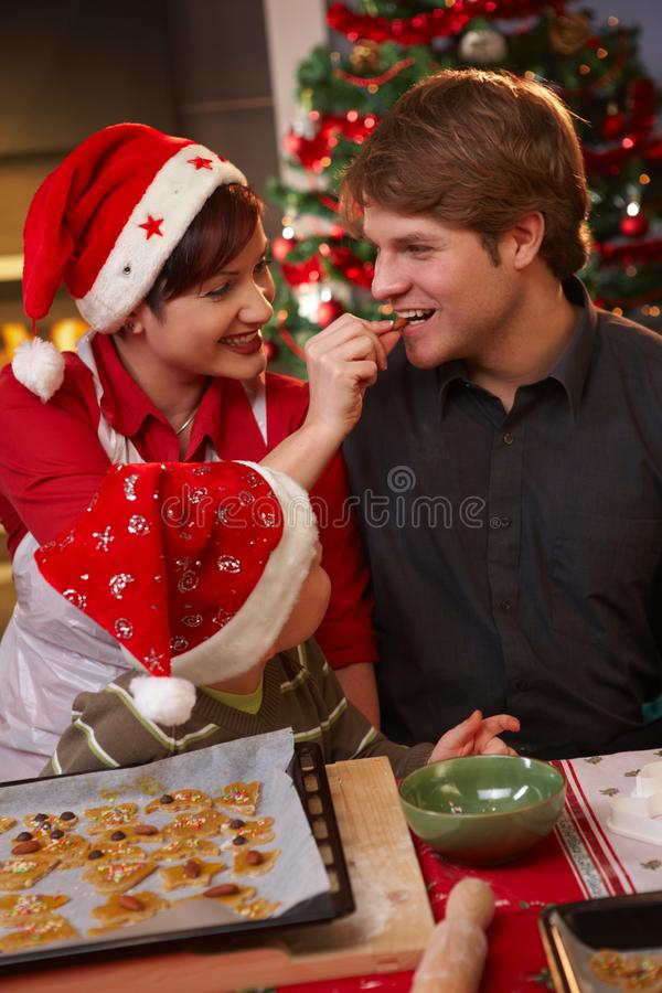 Dad tasting christmas cake with wife and kid royalty free stock image